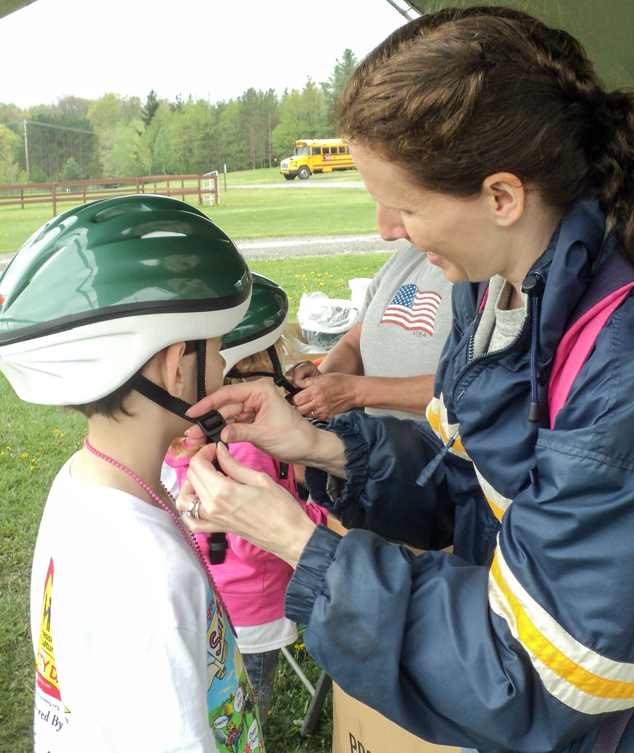 a woman adjusts the clasp on a childs safety helmet